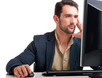 Jak banky komunikují s klienty. Srovnání komunikačních kanálů. Na snímku muž u počítače.