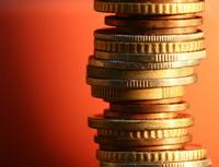 Banky připravují změny v sazebnících poplatků. Na snímku sloupec z mincí.