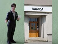 Aktuální marketingové akce bank. Na snímku pracovník banky a dveře do banky.