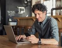 Obrázek: Muž smobilem a notebookem